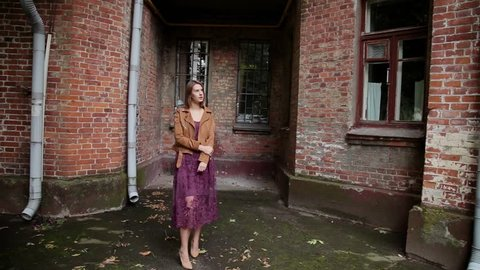 Very beautiful girl posing in the old courtyard of brick houses.