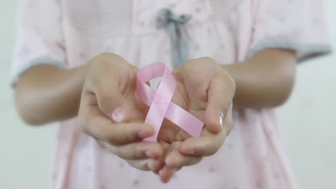 A girl with a pink ribbon for breast cancer survivor. Cancer awareness concept.