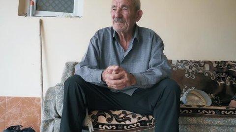 Elderly man talking. Active gesticulation. Closeup shot. Still camera