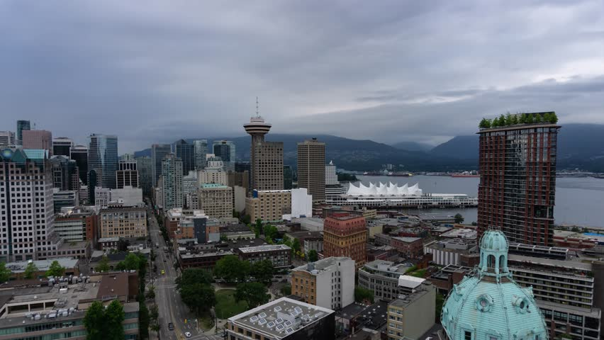 Aerial timelapse of a beautiful cityscape during a cloudy and rainy sunset. Taken in Downtown Vancouver, British Columbia, Canada.