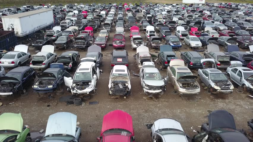 Aerial drone footage of a junk yard with row after row of wrecked cars.