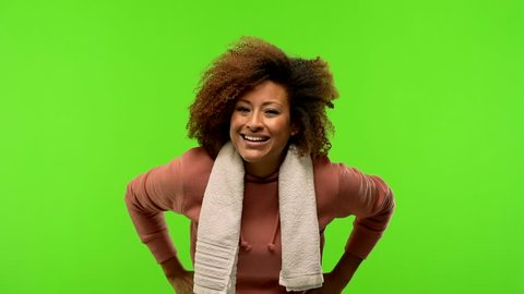 Young afro american fitness woman on a green chroma screen looking forward, scolding someone very angry
