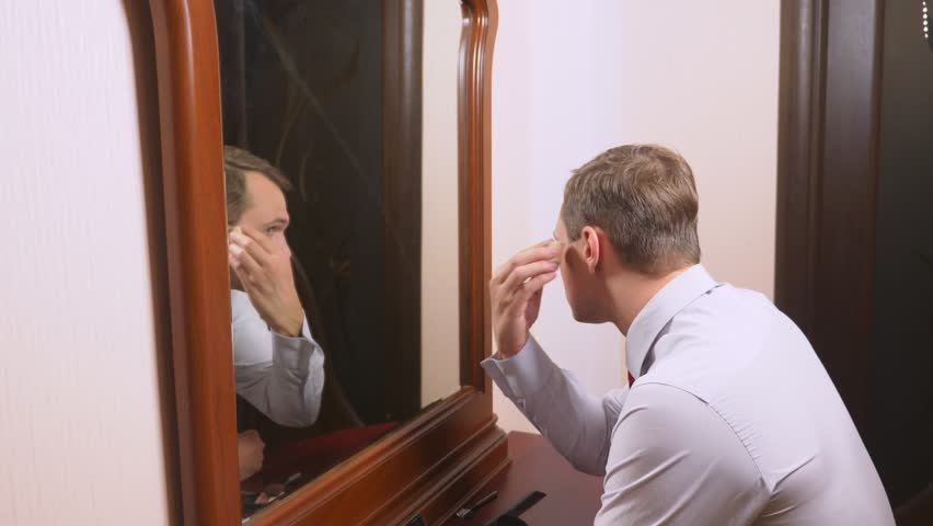 The concept of metrosexualism. a handsome man in front of a mirror takes care of his face. does the contouring of the face, everyday make-up. 4k, slow motion | Shutterstock HD Video #1017177265
