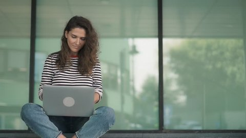 Serious young woman with long curly hair is sitting with crossed legs on building stairs and typing at her laptop keyboard. Handheld real time medium shot