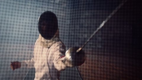 Duel, battle of two fencing athletes . Shot of the camera from inside the fencing mask . Two Professional Fencers Show Masterful Swordsmanship . Shot on ARRI ALEXA cinema camera .