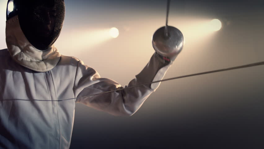 Fencer demonstrating jab, hit to heart . Fencing athletes duel . Two Professional Fencers Show Masterful Swordsmanship in their Foil Fight. Shot on ARRI ALEXA camera in slow motion .