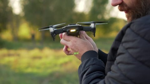 man calibrates in hands quadrocopter before flight