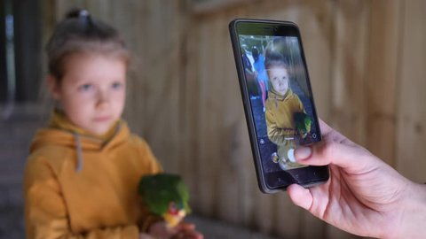 Mother take mobile phone pictures of child girl daughter holding feeding a parrot bird