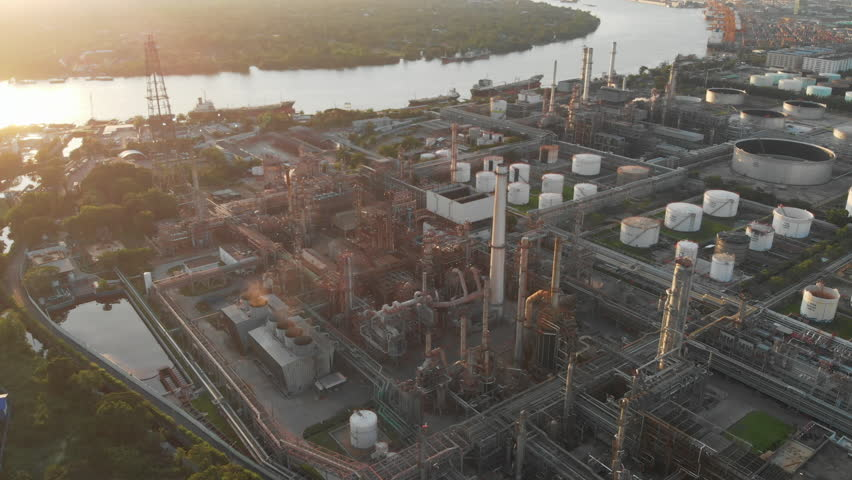 Aerial view over oil refinery factory or chemical plant standing next to big river with Bangkok city in background in evening. #1017279415