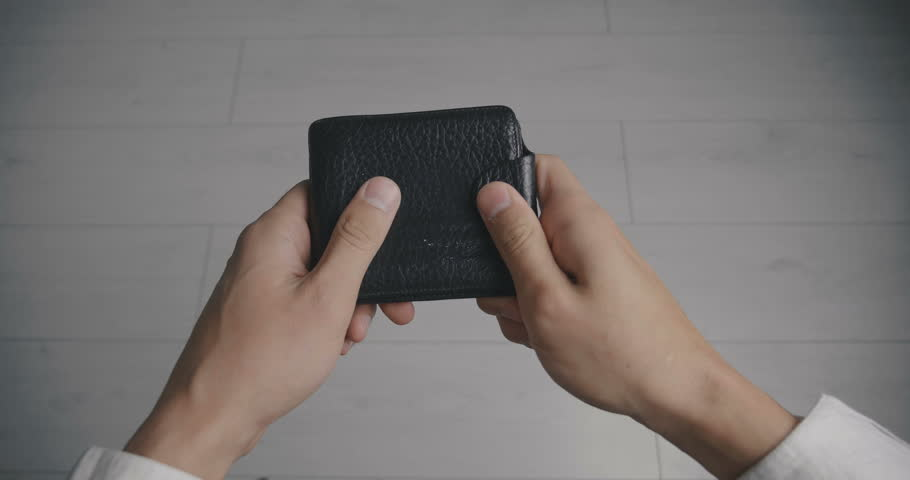 Close-up of a man's hand holding Leather Wallet Empty with one dollar banknote. The concept of lack of money. Lack of funds | Shutterstock HD Video #1017282655