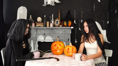 Young beautiful brunette having casual chat over hot cup of tea with creepy girl in scary Death Reaper Halloween costume