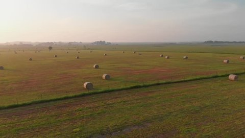 An aerial low flyover video of hay shortly after sunrise in a farmers field.