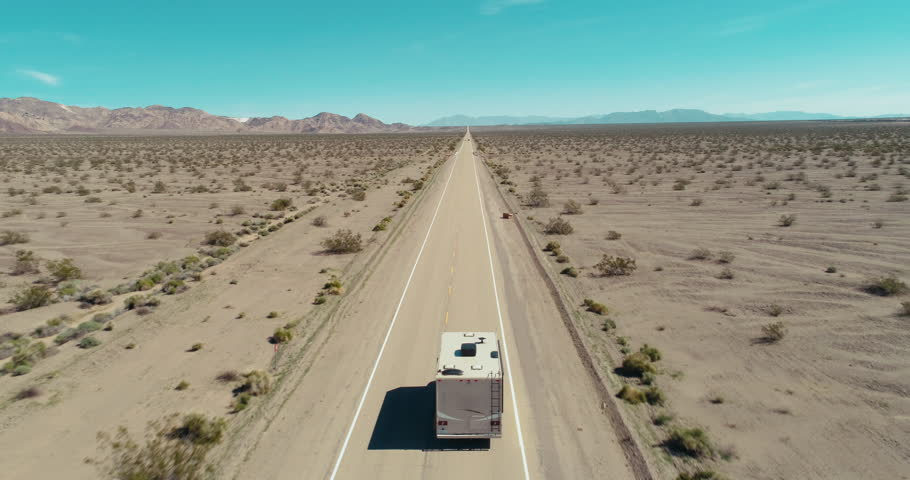 AERIAL - A drone follows a brown camper van from the back in the middle of the Mojave Desert and slowly gets closer to the van on route 66 on a clear blue day. | Shutterstock HD Video #1017388465