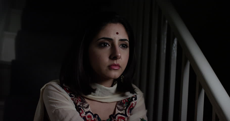 4K Young Indian woman who is worried about life problems sitting alone in the dark. Slow motion. | Shutterstock HD Video #1017412195
