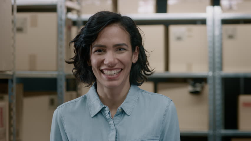 Portrait of the Beautiful Female Warehouse Inventory Manager Standing and Smiling Charmingly. Talented Career Woman Posing with Rows of Shelves Full of Cardboard Boxes and Parcels Ready for Shipment.  | Shutterstock HD Video #1017422845
