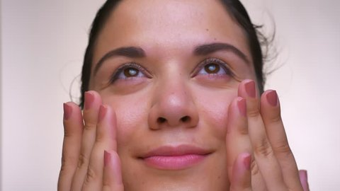 face portrat of awesoma caucasian female who is stroking herself with hands and looking up on white background