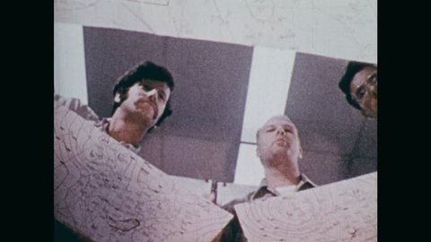 1970s: Globe large storm swirls, shadow passes over earth. Meteorologists spread out maps, charts, point with pen, finger.