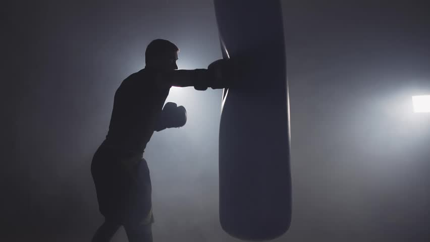 Alone boxer hits punching bag in dark gym in slow motion. Young man training indoors. Strong athlete in gym. Sport concept. Medium shot. Sportsman boxing in smoky studio | Shutterstock HD Video #1017517615