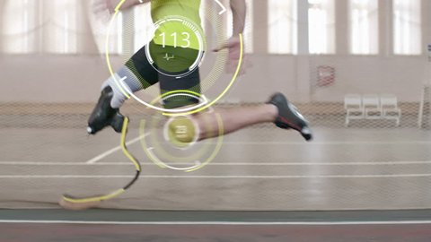 Tracking shot of paralympic athlete with prosthetic leg running on track; digitally animated pulse and speed projections appearing on his knee and hip