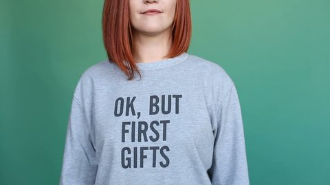 Crop of beautiful woman with bright dyed hair of red color wearing grey pullover with cynical message and pointing to it with hands. She is showing grimaces, flirting and winking at camera over