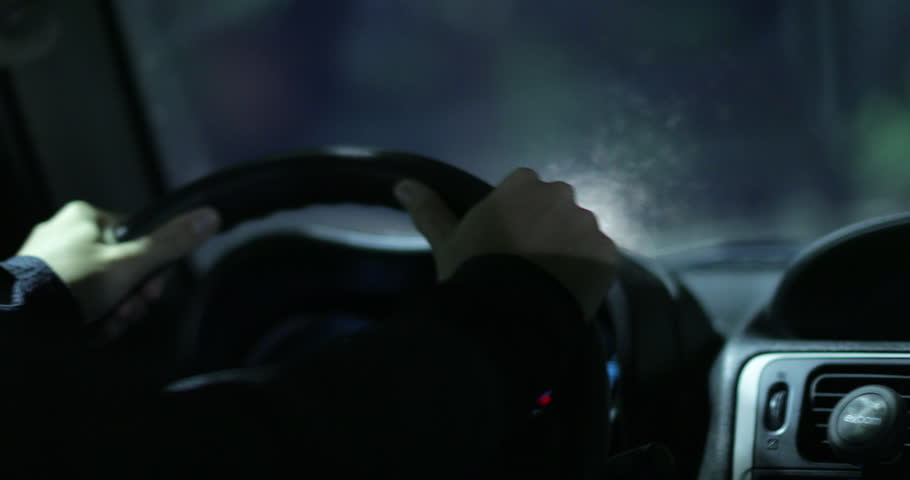 Hands holding steering wheel driving in the city at night #1017560395