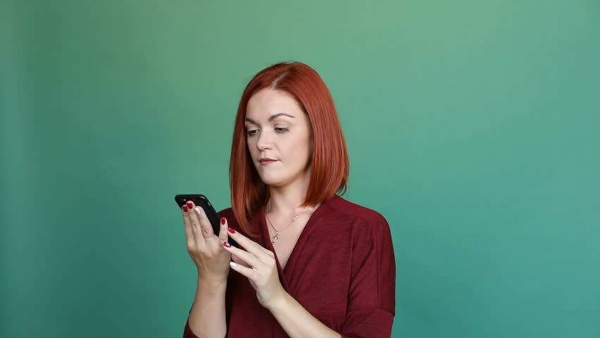 Studio portrait of attractive ginger woman in bright red blouse talking to her boyfriend or husband on cell phone, saying I LOVE YOU and blowing air kissess to the screen. Isolate on solid green backg