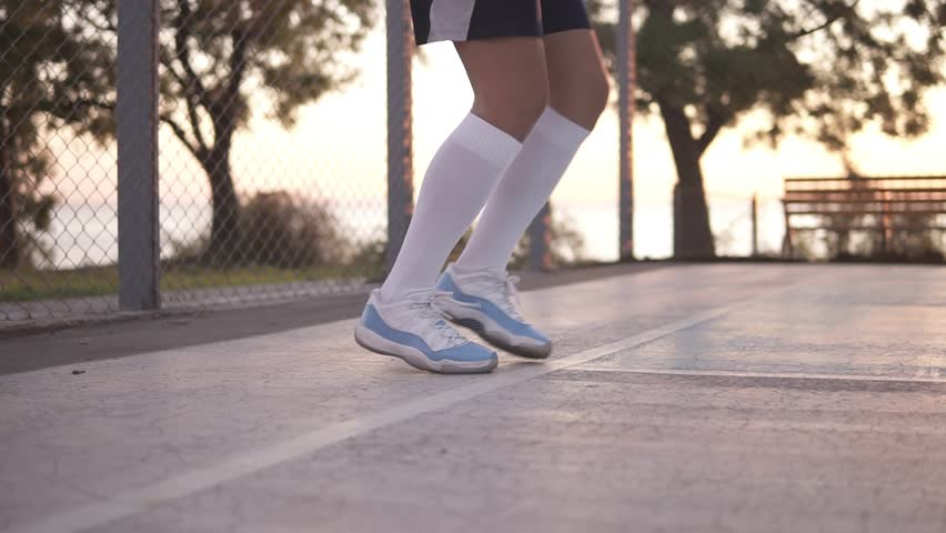 Close up of female basketball player legs in white golf socks doing dribbling exersice very quickly, run backwards, training outdoors on the local court #1017592855