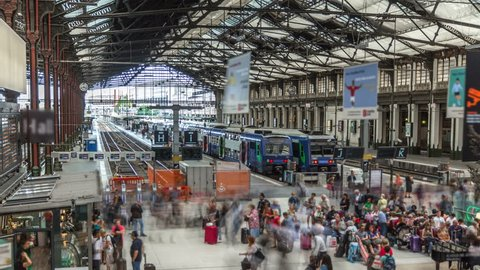 Railway Station with trains and hurrying people in Paris timelapse. Arrival an departure at Gare de Lyon a Paris, France.