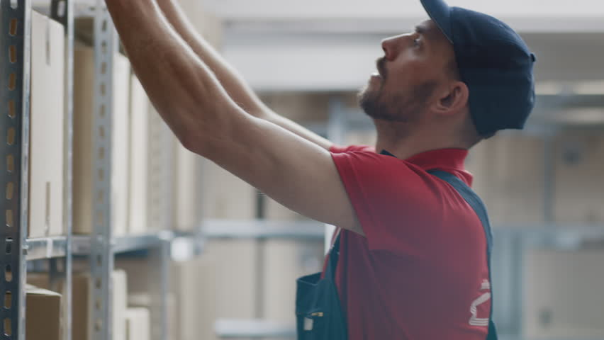 Warehouse Worker Collects Order by Taking Cardboard Boxes and Parcels of the Shelf and Putting them On a Trolley. | Shutterstock HD Video #1017604645