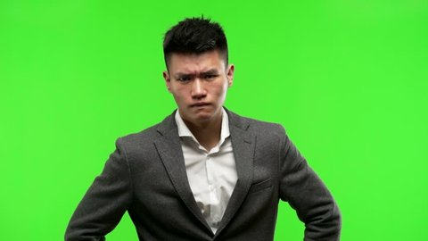 Young chinese business man on green chroma key background looking forward, scolding someone very angry