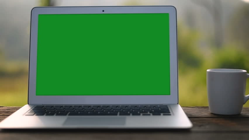 A laptop computer with a key green screen set on work office table.   Shutterstock HD Video #1017626905