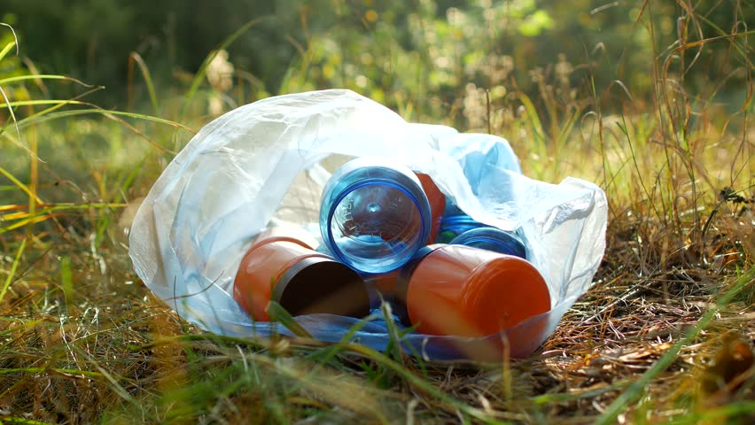 Garbage in a plastic bag plastic bottles lie on the grass, on the nature, garbage and nature, pollution of the nature, close-up | Shutterstock HD Video #1017636145