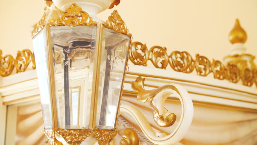 Baroque style vintage candle lamp on carriage close-up 4K. Dolly slide shot of candle lamp in focus, sliding from left to right with a carriage roof details in the background.