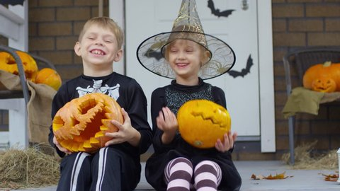 Happy little boy and girl in Halloween costumes sitting on decorated porch, holding jack-o-lanterns and laughing