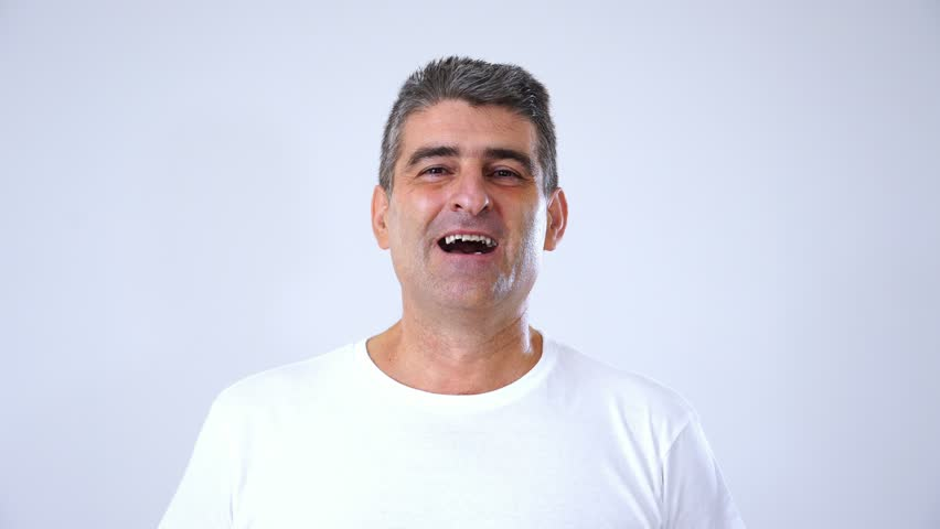 Happy excited laughing facial emotion expression of middle aged man 50s 60s year old man that is acting he just won the lottery or a big prize and is very excited in studio on grey background in face