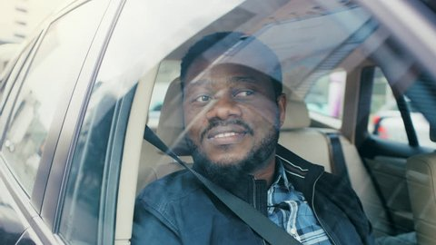 Handsome Young Black Man Rides on a Passenger Seat of a Car, Looks in Wonder out of the Window. Big City View Reflected in Window. Camera Mounted outside Moving Car.