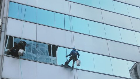 Window cleaners at work washing office building glass facade