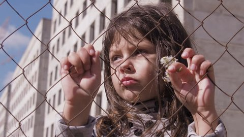Homeless child. Portrait of a homeless child. Refugee camp. Sad little girl behind the fence.  Child abuse.