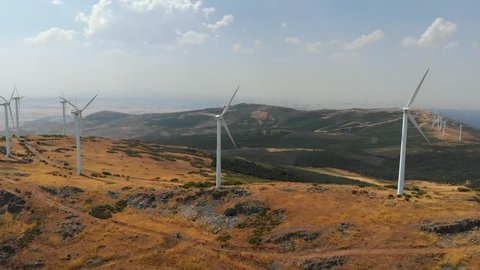 Aerial panoramic view of a windpower plant rotating airscrews in Spain. Scenery with hills and cloudy sky. 4K, UHD