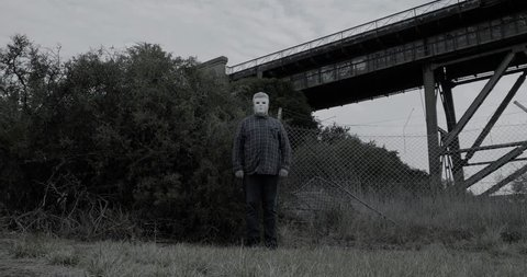 Creepy man wearing white halloween mask stands with head tilted in scary manner in front of bushes and old railway bridge