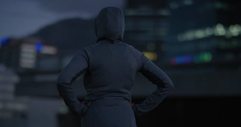 overweight indian woman runner resting exhausted after intense running workout training healthy fitness lifestyle in city at night wearing hoodie