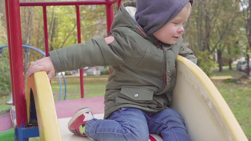 Cheerful boy riding down the hill on playground | Shutterstock HD Video #1017908065