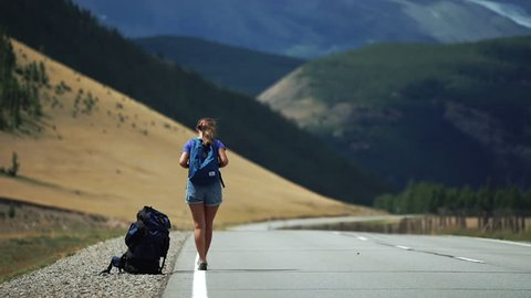 Traveler girl with a backpack and sunglasses is hitchhiking on a mountain road. There are snow mountains in the background. Back view