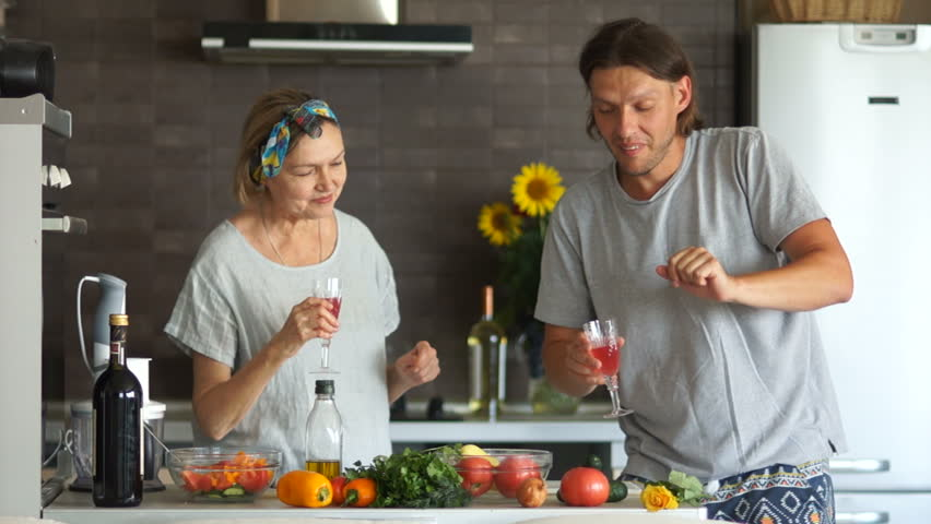 Mature woman and young man. A couple with an age difference prepare the salad in the kitchen, they relax to the music and drink wine from the glasses