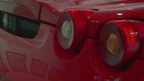Turning signals of red sport car blink. Close up view
