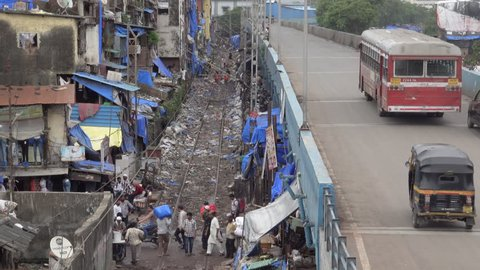 BANDRA, MUMBAI, INDIA - AUG 12: Slum area next to train tracks and busy road on August 12, 2018 in Bandra, Mumbai, India