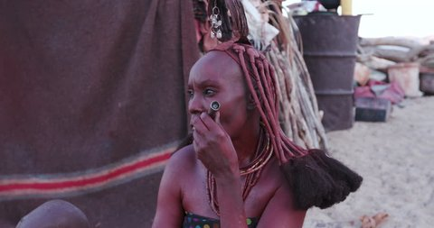 4K close-up view of Himba woman in traditional dress with young child, smoking a pipe outside their hut within their small compound, Namibia