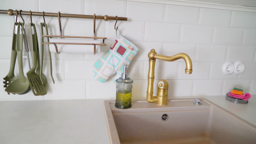 The golden faucet of the sink in the kitchen with the utensils and the pot holder hanging on the wall | Shutterstock HD Video #1018027135