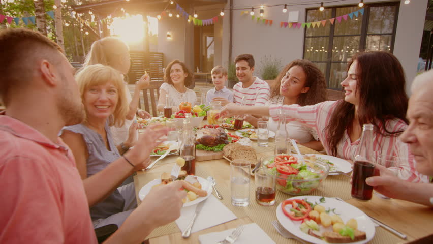 Big Family Garden Party Celebration, Gathered Together at the Table Relatives and Friends, Young and Elderly are Eating, Drinking, Passing Dishes, Joking and Having Fun. | Shutterstock HD Video #1018052485