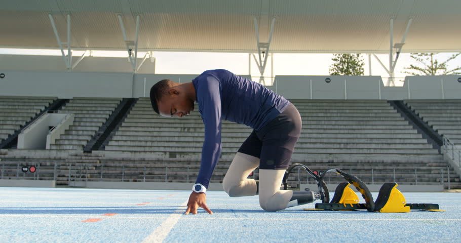 Side view of a disabled mixed-race athletic African american  getting ready for the race on a running track